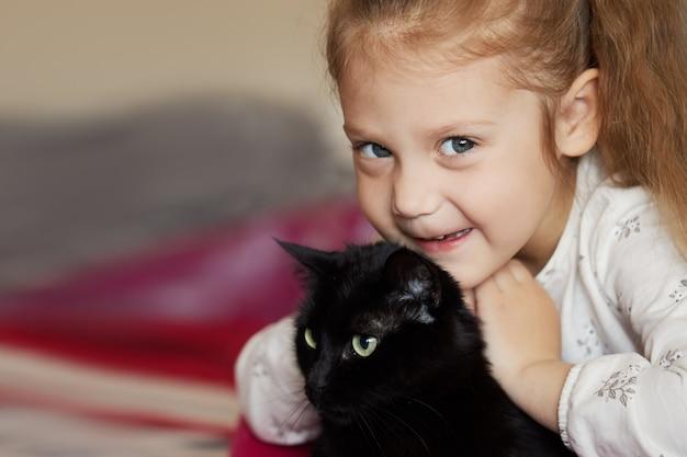 Portret małej uroczej dziewczynki, która ściska czarnego kota z czułością i miłością i uśmiecha się ze szczęścia