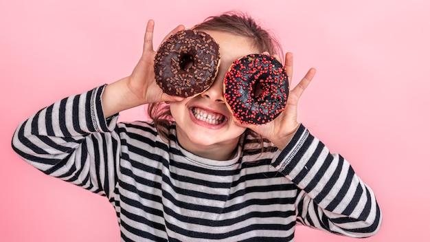 Portret małej uśmiechniętej dziewczyny brunetka z dwoma apetycznymi pączkami w dłoniach, zamyka oczy pączkami, na różowym tle.