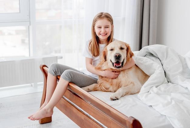 Portret małej uśmiechniętej dziewczyny przytulanie psa golden retriever w łóżku i patrząc w kamerę. dziecko w domu z pieskiem w godzinach porannych. zwierzę domowe z właścicielem