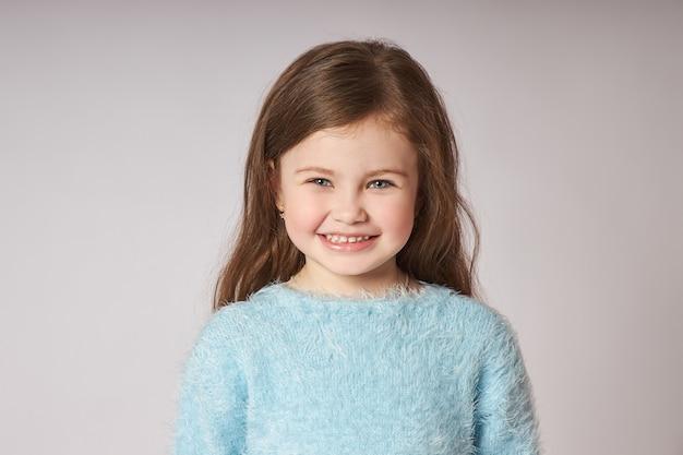 Portret małej uśmiechniętej dziewczyny. szczęśliwe emocje