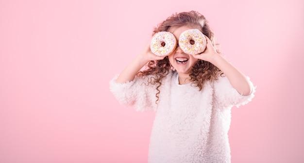 Portret małej uśmiechniętej dziewczyny z pączkami