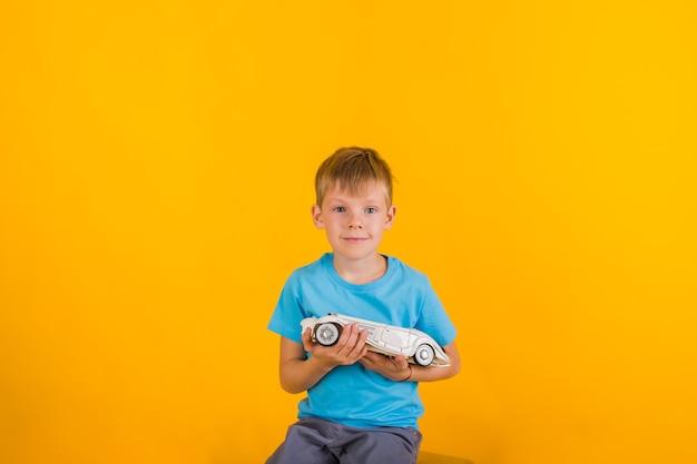 Portret malucha chłopiec bawi się białym samochodem retro i patrząc w kamerę na żółtym tle z miejscem na tekst