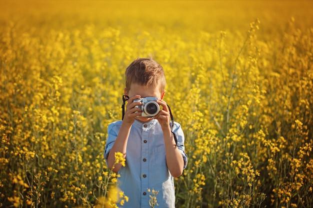 Portret mały chłopiec fotograf z kamerą na zmierzchu koloru żółtego pola tle