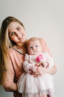 Portret mamy trzyma małą córeczkę z kwiatem różowego tulipana na jasnym tle. nowa koncepcja życia, miłości i wakacji. dzień kobiet. dzień matki.