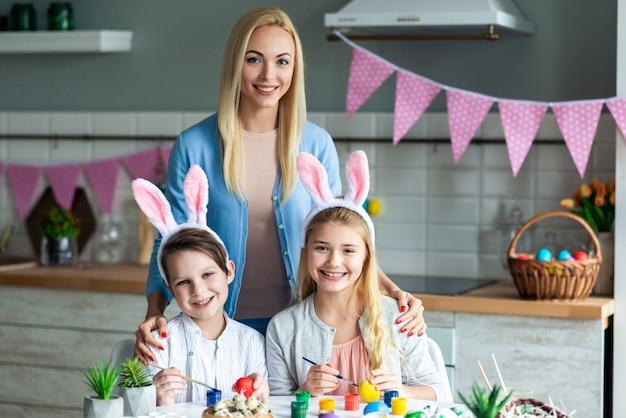 Portret mamy z dziećmi, wielkanocny wystrój kuchni.