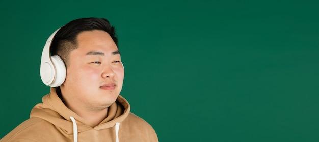 Portret mans azjatyckich izolowanych na zielonej ścianie z copyspace