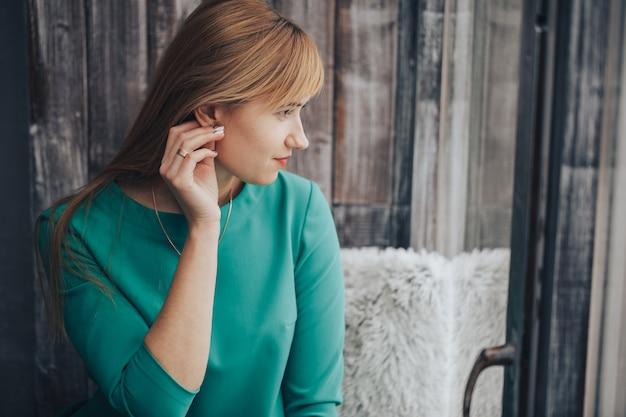 Portret marzycielska kobieta w zielonej sukni wygląda przez okno