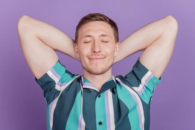 Portret marzycielskiego, sennego pozytywnego faceta, który ręce sen sen głowy na fioletowym tle