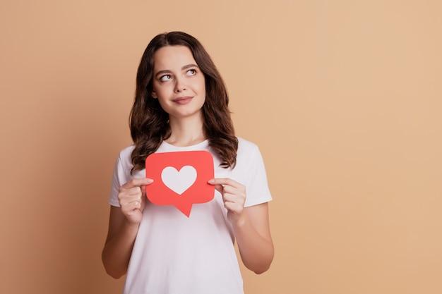 Portret marzycielskiej ciekawej dziewczyny trzymaj ikonę powiadomienia serca wygląda na pustą przestrzeń na białym tle na beżowym tle