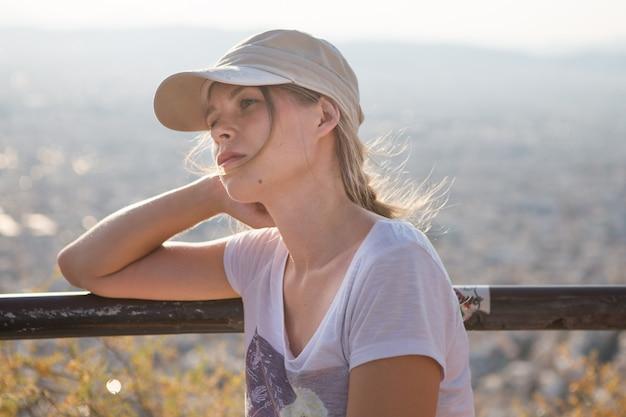 Portret marzycielskiej i atrakcyjnej powietrznie dziewczyny w czapce jest figlarny i beztroski z pięknym uśmiechem w słoneczny dzień aten z górą lycabettus w grecji widzianą drogą powietrzną.
