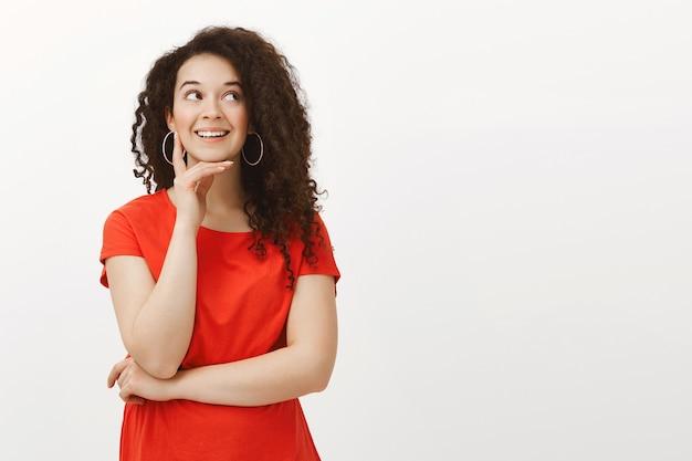Portret marzycielskiej przystojnej stylowej kobiety z kręconymi włosami w czerwonej sukience, uśmiechającej się radośnie, patrząc na bok, trzymając dłoń na brodzie