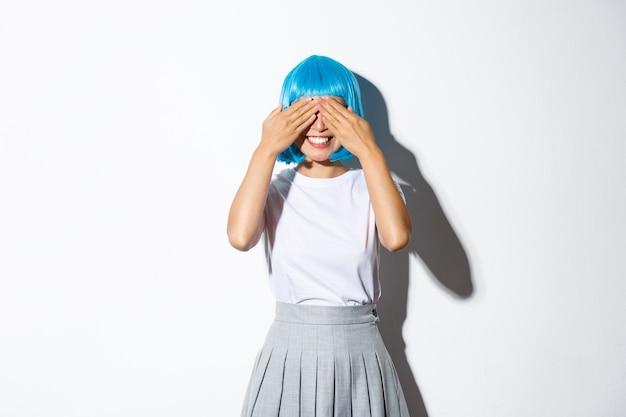 Portret marzycielskiej ślicznej azjatki w niebieskiej peruce zamyka oczy rękami i uśmiecha się, czeka na niespodziankę, świętuje halloween na imprezie.
