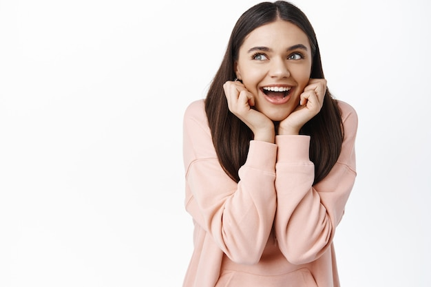 Portret marzycielskiej szczęśliwej kobiety wyobrażającej coś, opartej na rękach i uśmiechającej się zamyślonej, patrzącej z zainteresowaniem w lewy górny róg, marzące, biała ściana