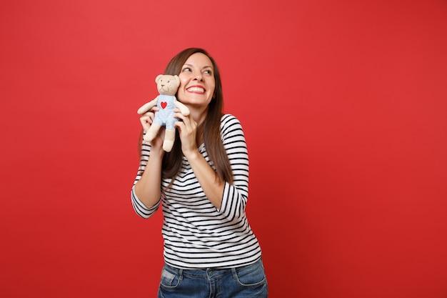 Portret marzycielskiej uśmiechniętej młodej kobiety w pasiastych ubraniach, patrząc w górę, trzymając pluszową zabawkę pluszowego misia