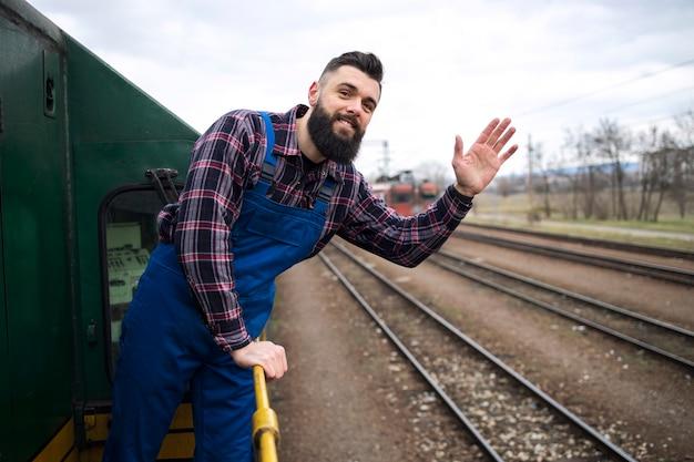 Portret maszynisty pociągu lub lokomotywy macha na stacji