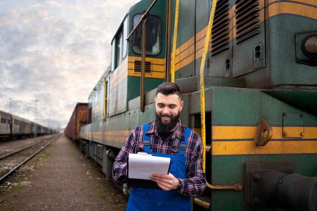 Portret maszynisty stojącego przy lokomotywie na stacji kolejowej i trzymając harmonogram odjazdów