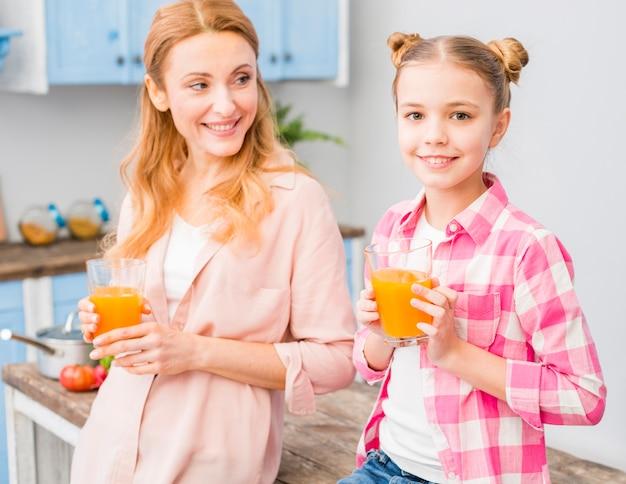 Portret matka i córka trzyma szkło sok w ręce