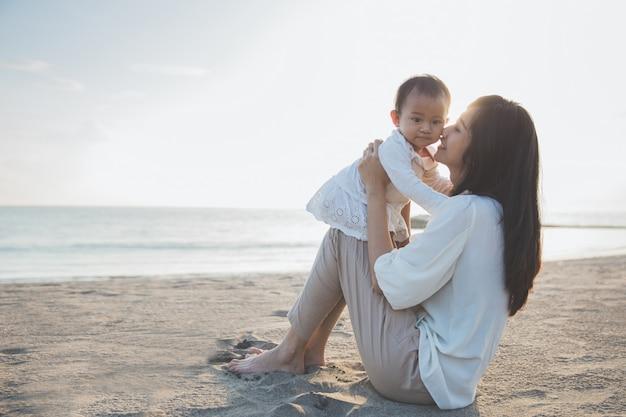 Portret matka i dziecko w plaży przy zmierzchem