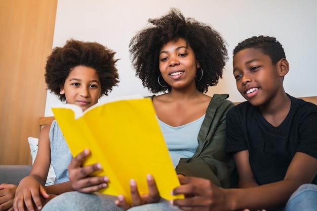 Portret matki afro amerykanina czytająca książkę do swoich dzieci w domu. koncepcja rodziny i stylu życia.