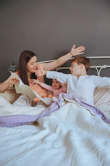 Portret matki, czytanie książki z opowieściami do jej córki i syna dzieci siedzących w łóżku. koncepcja wypoczynku rodzinnego weekendu.