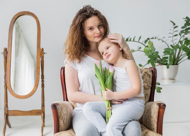 Portret matki i córki obsiadanie na ręki krześle