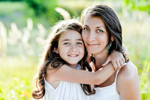 Portret matki i córki przytulanie. natura, słoneczna pogoda