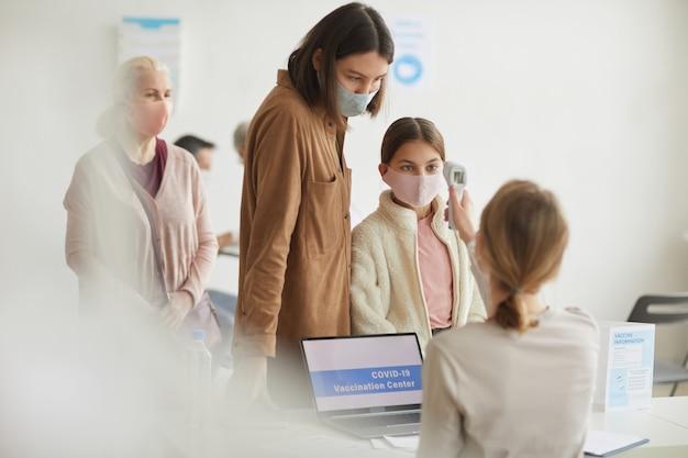 Portret matki i córki rejestrujących się na szczepionkę przeciw covid w klinice medycznej, kopia przestrzeń