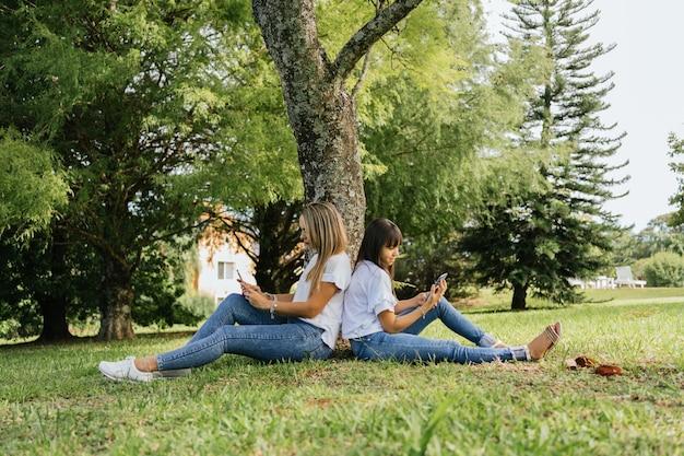 Portret matki i córki siedzącej pod drzewem.