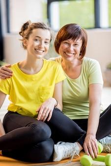 Portret matki i córki w strojach sportowych siedzących razem po treningu w pomieszczeniu