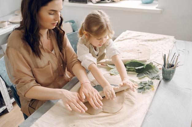 Portret matki i małej dziewczynki kształtująca glina wpólnie