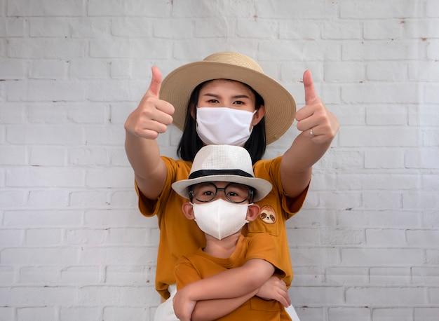 Portret matki i syna pokazuje kciuk w górę i jest ubranym ochronną maskę próbuje ochraniać przed koronawirusem