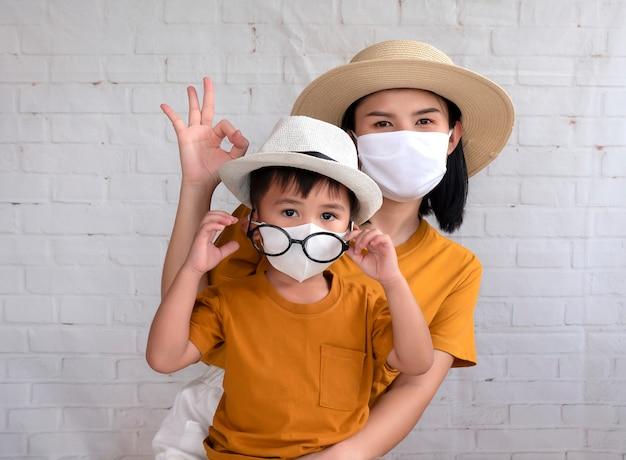 Portret matki i syna pokazuje ok znaka i jest ubranym ochronną maskę próbuje chronić przed koronawirusem