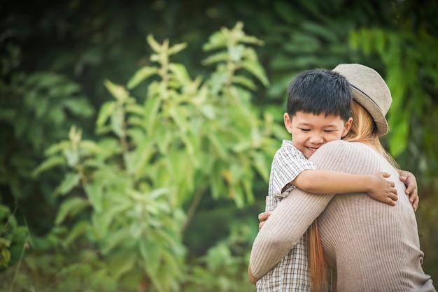 Portret matki i syna szczęśliwy cuddle wpólnie w parku. pojęcie rodziny.