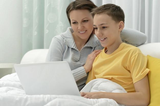 Portret matki i syna wspólnie korzystających z laptopa