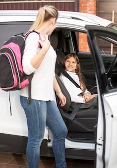 Portret matki patrzącej na córkę siedzącą w samochodzie