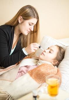 Portret Matki Podającej Leki Do Nosa Chorej Córce Leżącej W łóżku Premium Zdjęcia