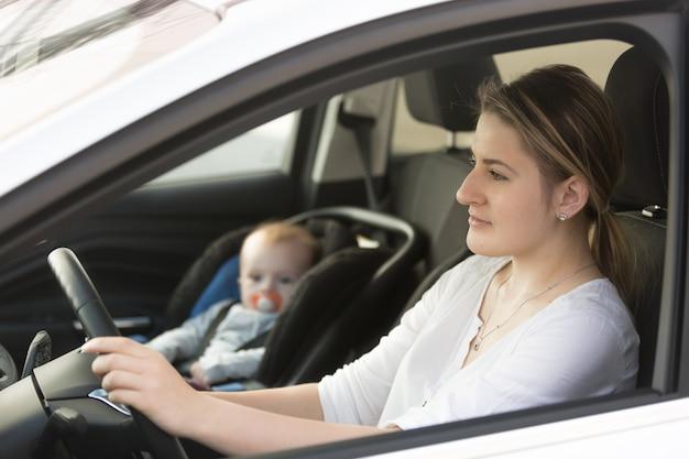 Portret matki prowadzącej samochód z dzieckiem siedzącym na przednim siedzeniu