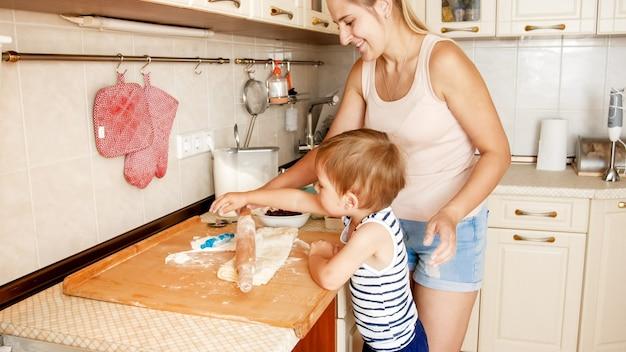 Portret matki z 3-letnim synem piekącym ciasteczka w kuchni o poranku