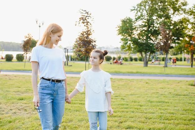 Portret matki z córką w letnim parku. obraz z selektywną ostrością, efektami szumów i tonowaniem. skoncentruj się na dziewczynie i mamie.