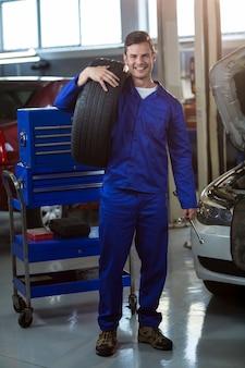 Portret mechanik niosąc oponę
