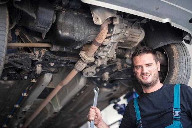 Portret mechanika samochodowego z narzędziem klucza pracującego pod pojazdem w warsztacie samochodowym