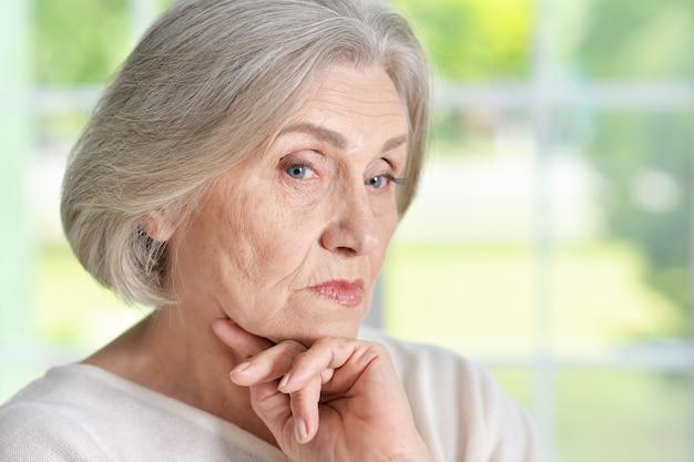 Portret melancholijnej starszej kobiety z bliska