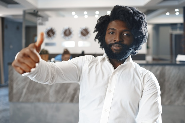 Portret menedżera hotelu lub gościa szczęśliwego afrykańskiego mężczyzny stojącego w hotelu