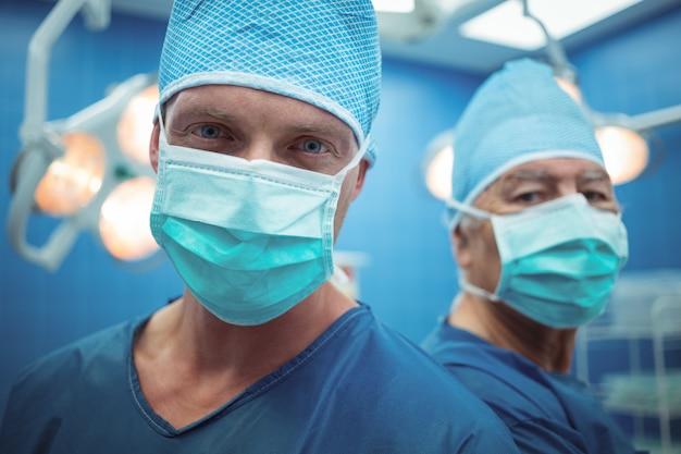 Portret męscy chirurdzy jest ubranym chirurgicznie maski funkcjonującego teatr