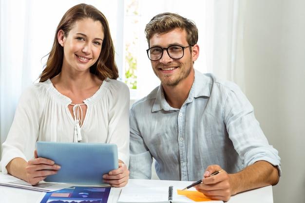 Portret męscy i żeńscy koledzy używa cyfrową pastylkę przy biurem