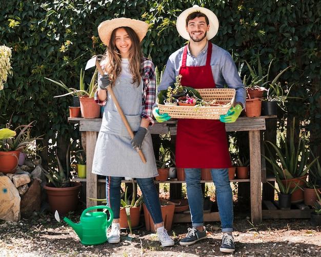 Portret męscy i żeńscy ogrodniczki mienia narzędzia i kosz w ogródzie