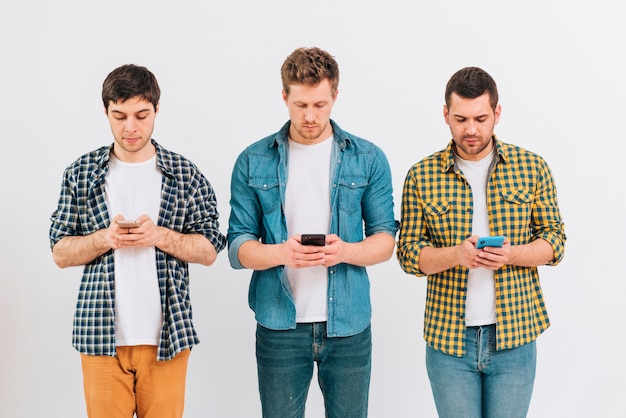 Portret męscy przyjaciele stoi przeciw białemu tłu używać telefon komórkowego