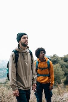 Portret męscy wielo- etniczni przyjaciele wycieczkuje w lesie