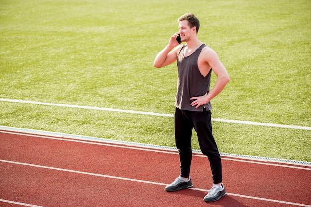 Portret męska atleta stoi na biegowym śladzie opowiada na mądrze telefonie