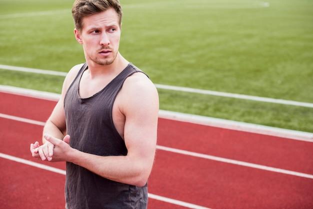 Portret męska atleta stoi na biegowym śladzie patrzeje daleko od